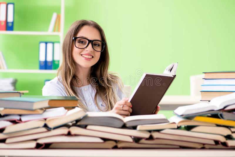 Den unga kvinnliga studenten som förbereder sig för examina med många böcker royaltyfria foton