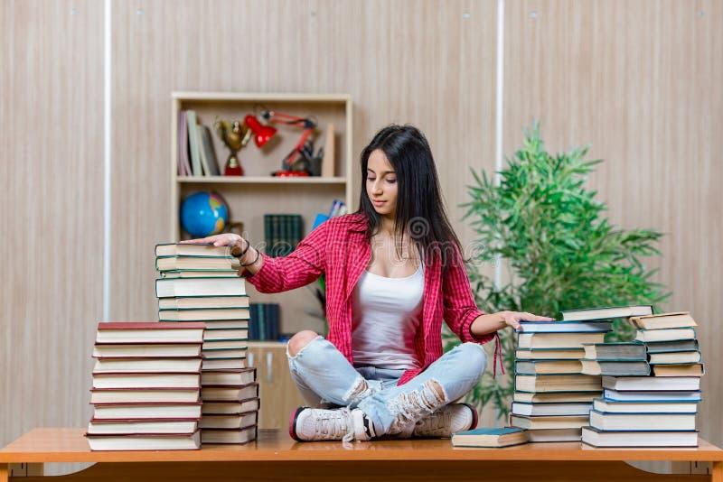 Den unga kvinnliga studenten som förbereder sig för högskolaskolaexamina arkivbilder
