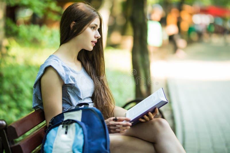 Den unga kvinnliga studenten som sitter på bänk, och läseboken parkerar in arkivfoto