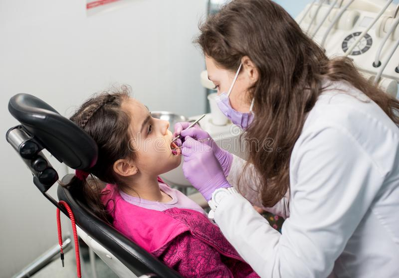 Den unga kvinnliga tandläkaren kontrollerar upp tålmodiga flickatänder på det tand- kontoret arkivfoton