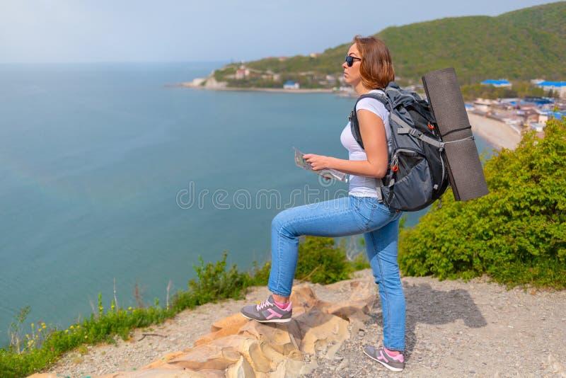 Den unga kvinnliga turisten klättrar berget och kontrollerar omgivningen med en översikt i hand royaltyfria foton