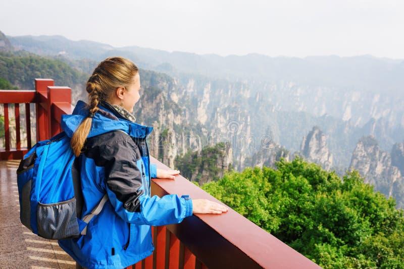 Den unga kvinnliga turisten med blått vandrar att tycka om bergsikt arkivbild