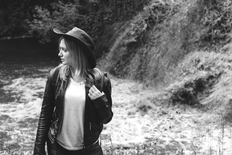 Den unga kvinnliga turisten med ryggsäck- och cowboyhatten som ser floden, tvättade bort bron, korsningen var omöjlig djupt arkivfoto