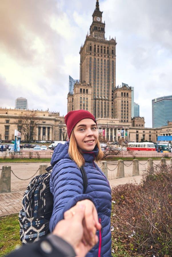 Den unga kvinnliga turisten nära slotten av kultur och vetenskap i Warszawa, följer mig begreppet Ha en lycklig semester i Polen arkivbild