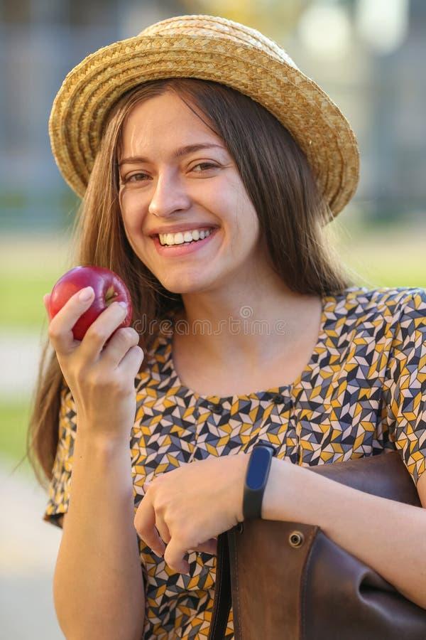 Den unga kvinnlign äter äpplet Den unga kvinnlign har lunch utomhus royaltyfri foto
