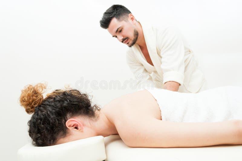 Den unga kvinnlign får en kroppmassage av den stiliga mannen royaltyfria bilder