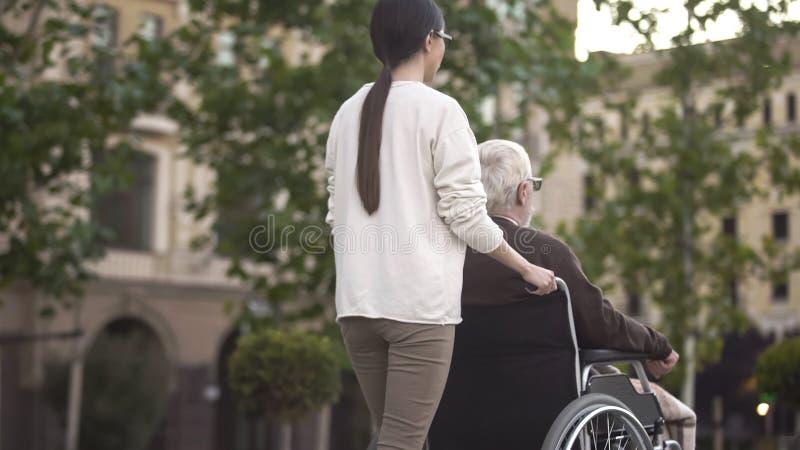 Den unga kvinnlign går på med den rörelsehindrade äldre mannen i rullstolen, familjservice arkivfoto