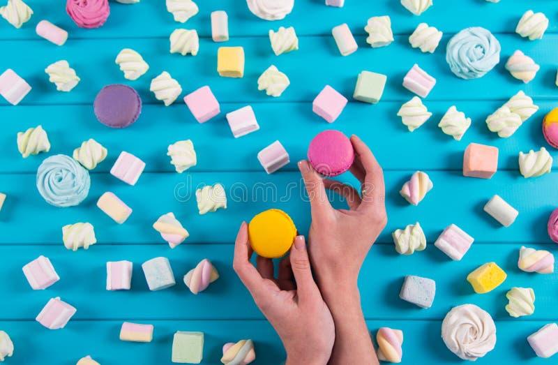 Den unga kvinnlign räcker att rymma två vibrerande makron med mycket fyrkantig färgrik marshmallow på blå bakgrund arkivfoton