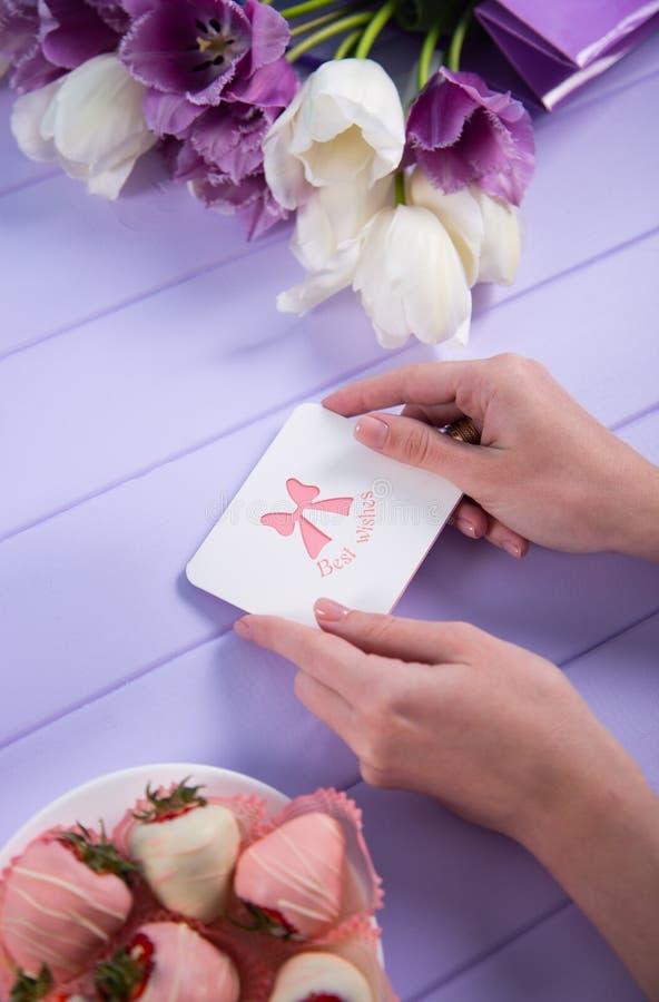 Den unga kvinnlign räcker det hållande hälsningkortet nära bukett av den purpurfärgade och vita tulpan och jordgubben i choklad royaltyfria bilder