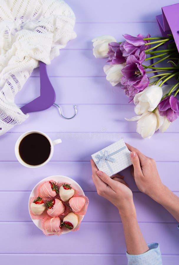 Den unga kvinnlign räcker den hållande gåvaasken nära buketten av purpurfärgade och vita tulpan, koppen kaffe, jordgubben i chokl fotografering för bildbyråer