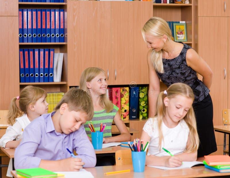 Den unga läraren hjälper studenter av grundskola för barn mellan 5 och 11 år i examen arkivbild