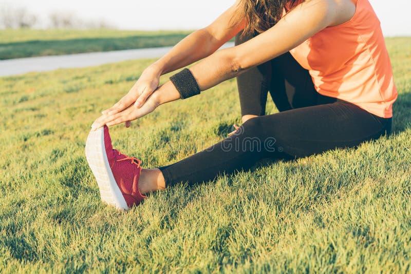Den unga löparekvinnan som sträcker ben för inkörd, parkerar Stäng upp den idrotts- och sunda flickan som bär vita och rosa gymna royaltyfri fotografi