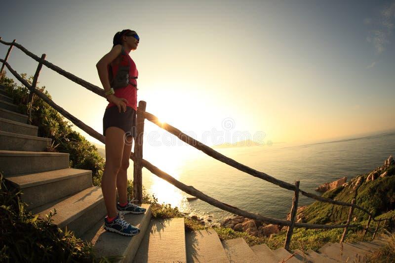 Den unga löparen för konditionkvinnaslingan tycker om sikten på sjösidaberget arkivfoto