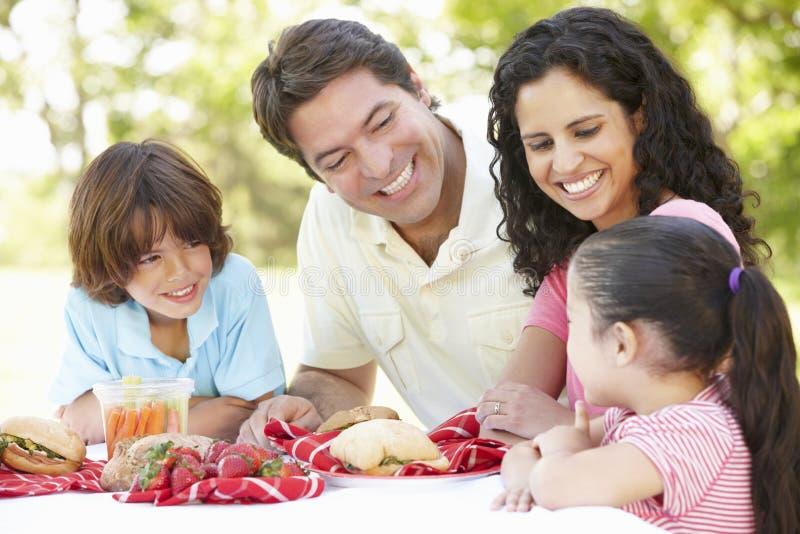 Den unga latinamerikanska familjen som tycker om picknicken parkerar in arkivbild