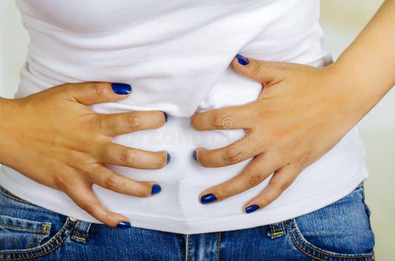 Den unga latinamerikanska kvinnan som trycker på hennes buk som lider menstruations- period, smärtar, det kvinnliga vård- begrepp royaltyfri fotografi