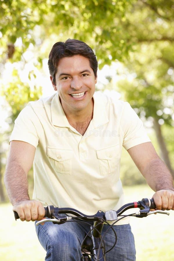 Den unga latinamerikanska mannen som in cyklar, parkerar fotografering för bildbyråer
