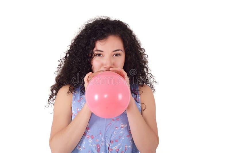 Den unga latinska kvinnan blåser ballongen arkivfoto