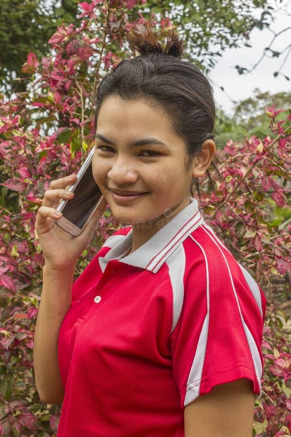 Den unga le asiatiska kvinnan talar på telefonen royaltyfri fotografi