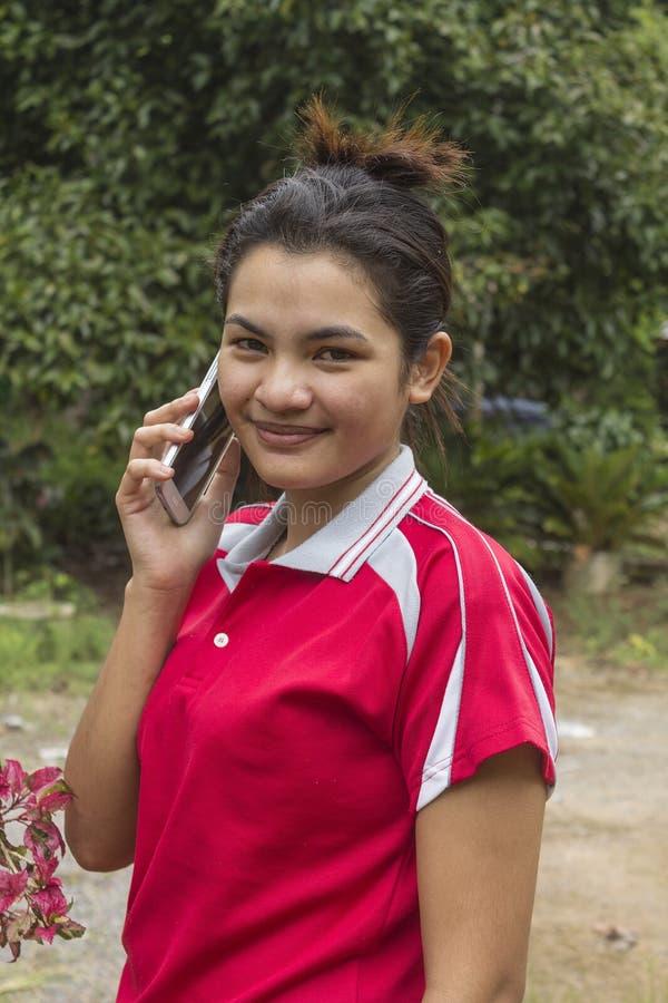 Den unga le asiatiska kvinnan talar på telefonen fotografering för bildbyråer