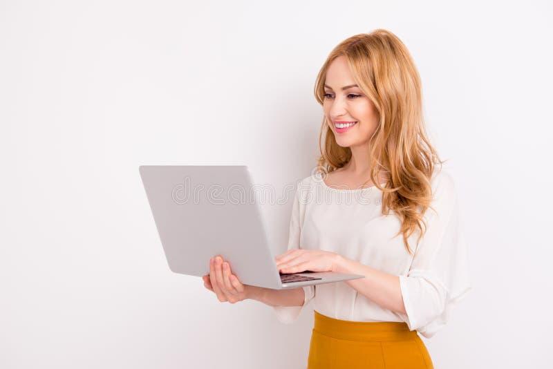 Den unga le bärbara datorn och maskinskrivning för blond kvinna hållande på det isolerade på vitt bakgrundskopieringsutrymme Se b royaltyfria foton