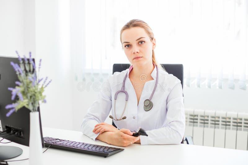 Den unga le doktorn som sitter på skrivbordet på en svart stol med hennes armar, korsade arkivfoton