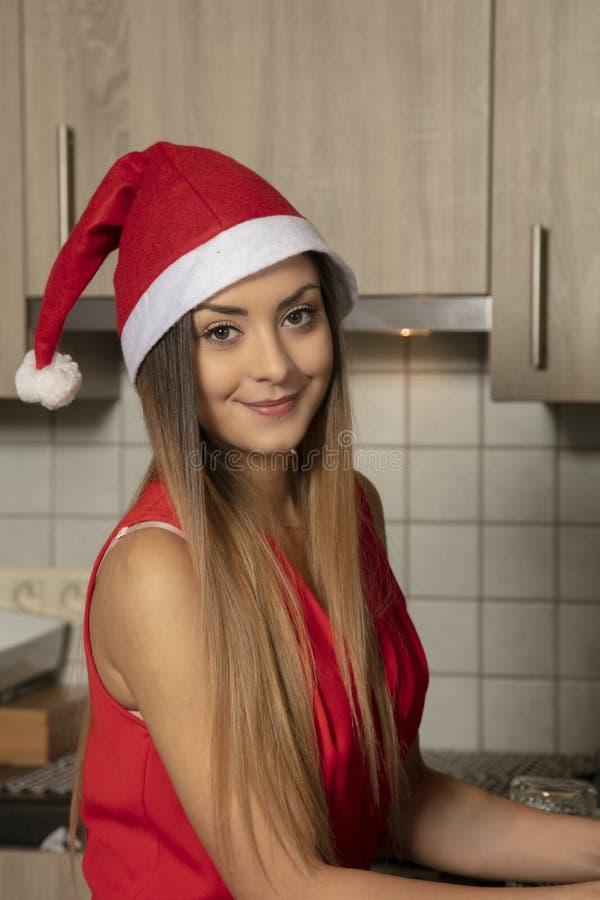 Den unga le flickan i en röd klänning får klar för jul royaltyfri bild