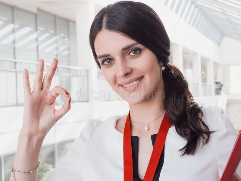 Den unga le flickan som göras lyckade arbetsshower, gör en gest upp den stora tummen Härliga le affärskvinnaStanding Against Whit royaltyfri foto