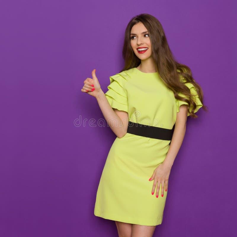 Den unga le kvinnan i klänning för limefruktgräsplan ger upp tummen royaltyfria bilder