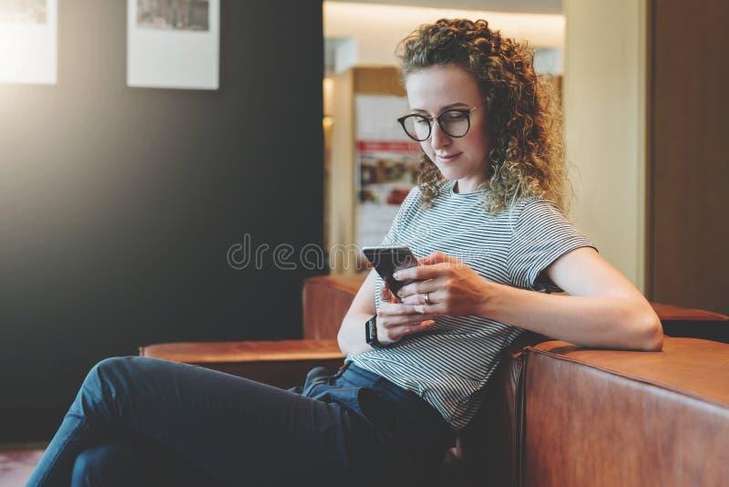 Den unga le kvinnan med lockigt hår i glasögon sitter i väntande rum på soffan och använder smartphonen Tryck för dina T-tröja royaltyfri fotografi