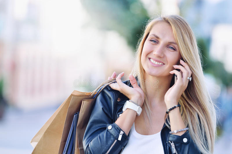 Den unga le kvinnan med shoping påsar talar vid mobiltelefonen royaltyfria bilder