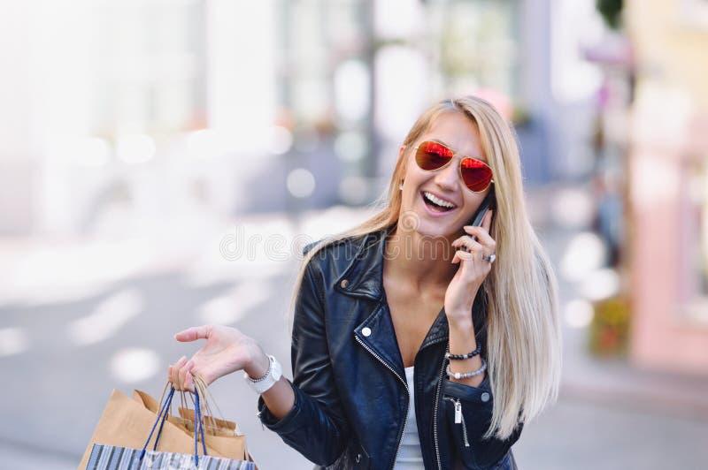 Den unga le kvinnan med shoppingpåsar talar vid mobiltelefonen royaltyfria foton