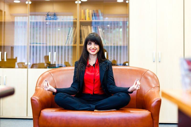 Den unga le kvinnan mediterar på soffan i regeringsställning royaltyfria bilder