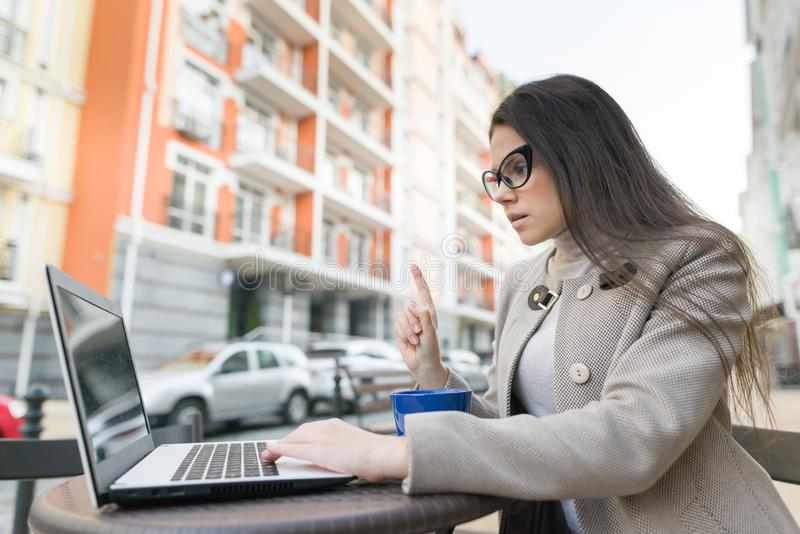 Den unga le kvinnan visar upp pekfingret, uppmärksamhetidén eureka Stads- höstbakgrund, flicka med exponeringsglas i utomhus- kaf royaltyfri bild