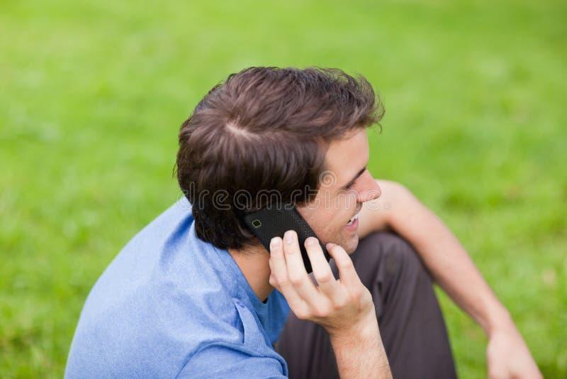Den unga le manen som talar på ringa, fördriver sammanträde i en parkera royaltyfri bild