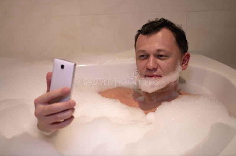 Den unga le mannen sitter badrummet gör skägget tar selfie arkivbild