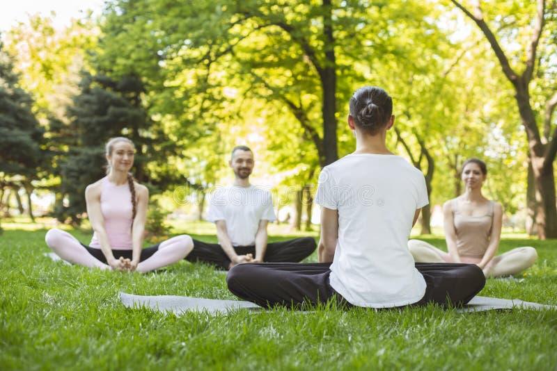 Den unga le praktiserande yogakursen för folk med instruktören parkerar in royaltyfri bild