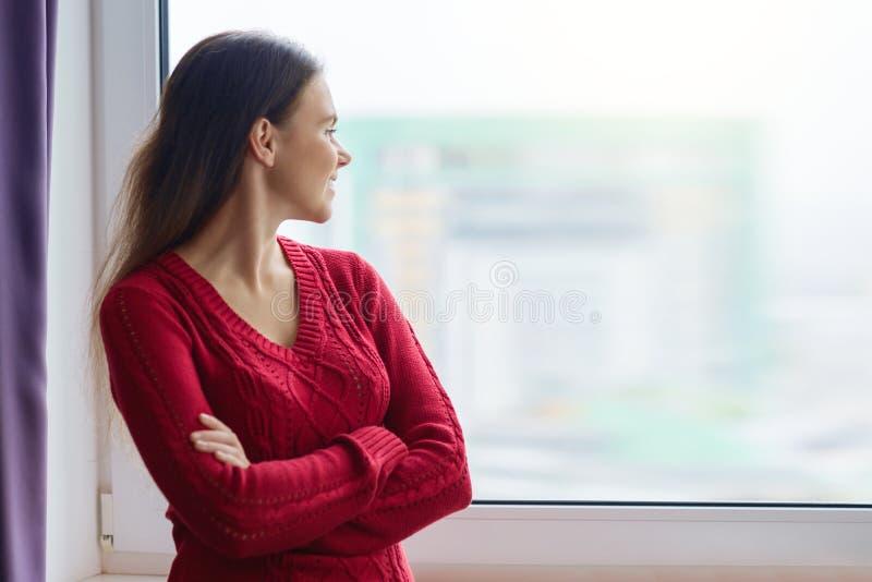Den unga le säkra kvinnan står nära fönstret, kvinnlig korsade hennes armar, kvinna i en stucken tröja arkivbild