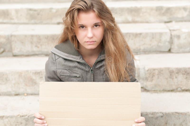 Den unga ledsna flickan som är utomhus- med tom papp, undertecknar. royaltyfri fotografi