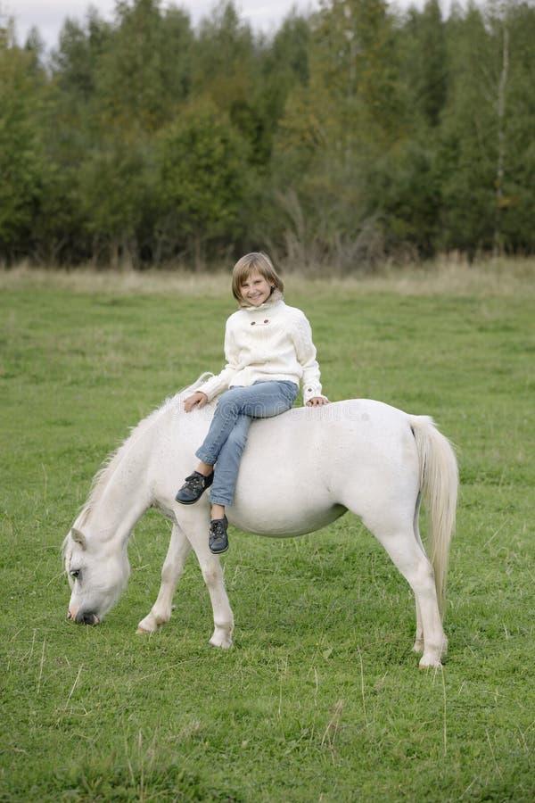 Den unga lilla flickan i vitt sitta för tröja och för jeans kors-lade benen på ryggen på en vit häst Livsstilstående arkivbilder