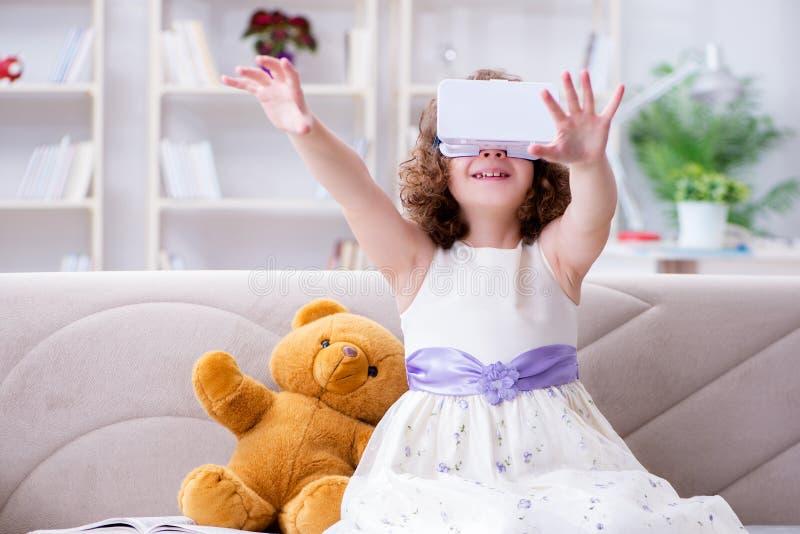 Den unga lilla flickan med vrvirtuell verklighetexponeringsglas fotografering för bildbyråer
