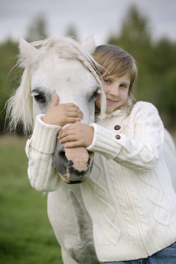 Den unga lilla flickan omfamnar en vit häst över huvudet Livsstilstående arkivbild