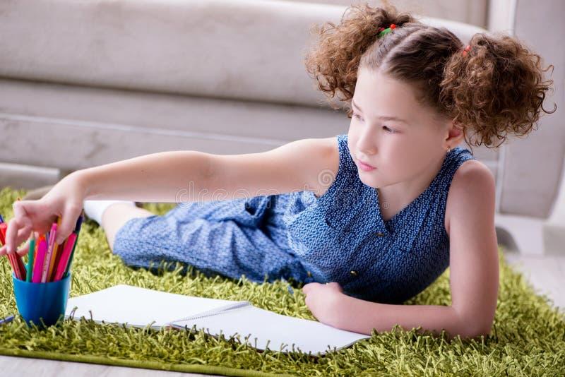 Den unga liten flickateckningen på papper med blyertspennor arkivbild