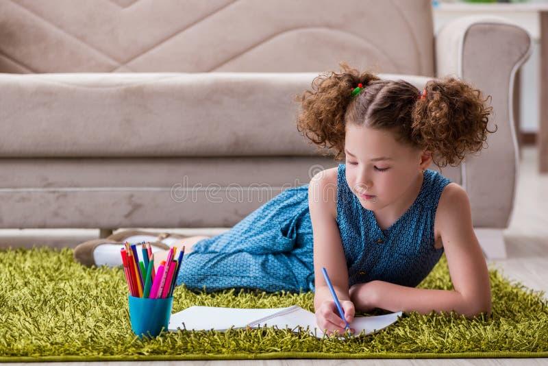 Den unga liten flickateckningen på papper med blyertspennor fotografering för bildbyråer