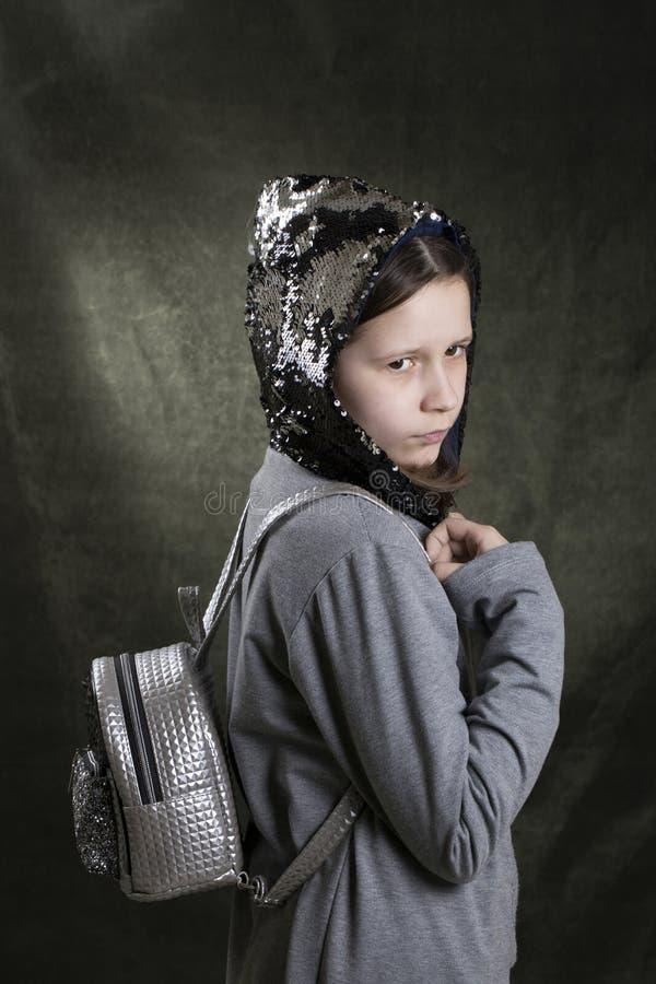 Den unga ljusa modellen med en ryggsäck på baksidan poserar fotografering för bildbyråer