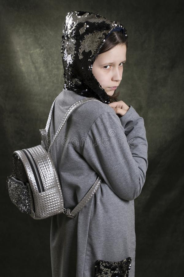 Den unga ljusa modellen med en ryggsäck på baksidan poserar royaltyfri fotografi