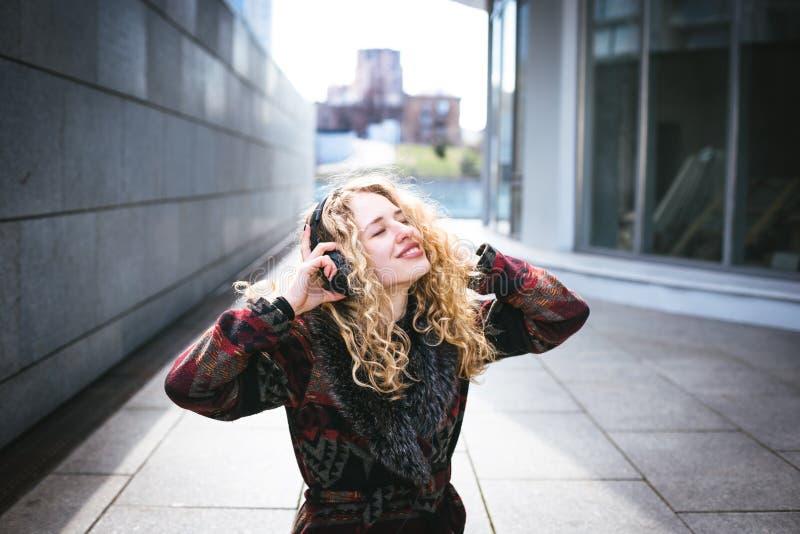Den unga lockiga kvinnan som använder hennes telefon och, kopplar av i staden arkivbilder