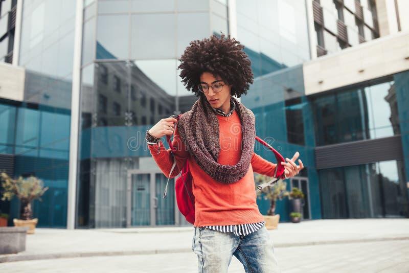 Den unga lockiga svarta afrikanska amerikanen med exponeringsglas går till och med stadsgatorna mot en skyskrapa royaltyfria bilder