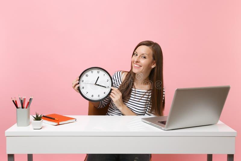 Den unga lyckade kvinnan i tillfällig kläder rymmer den runda ringklockan sitter arbete på det vita skrivbordet med den moderna P royaltyfri bild