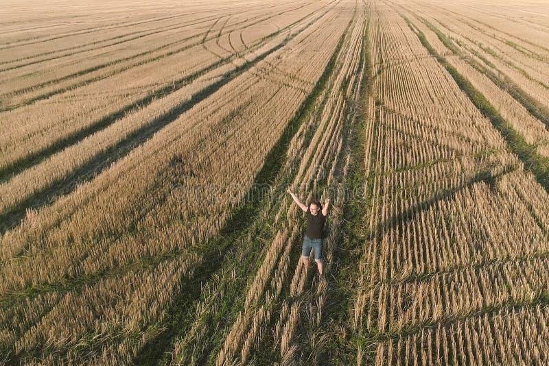 Den unga lyckade lyckliga manvinnaren jublar på fältet, beväpnar utsträckt flyg- panorama- sikt fotografering för bildbyråer