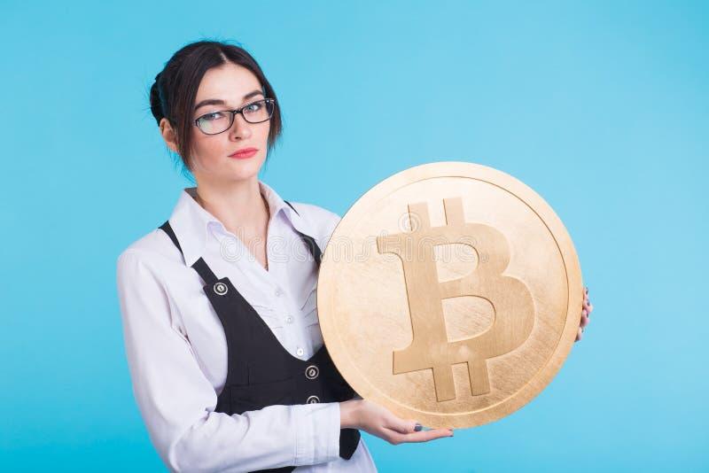 Den unga lyckade säkra kvinnan med exponeringsglas rymmer en stor bitcoin i hennes hand royaltyfria bilder